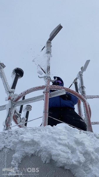 Observer Nicole de-icing the instrumentation on top of the tower in sustained 89 mph winds with gusts around 112 mph